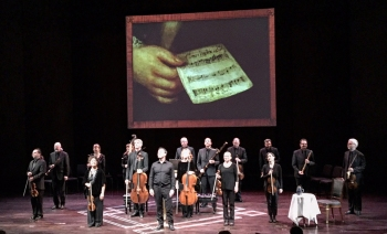 Blair Williams and the orchestra at the end of a tour performance, in front of the image of the canon held by Bach in the Haussmann portrait.