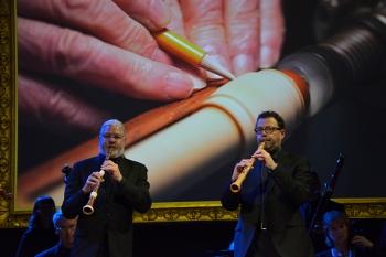 Image of the hands of oboe maker Harry vas Dias, projected behind Tafelmusik oboists John Abberger & Marco Cera.