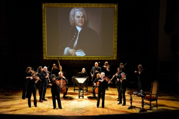 Tafelmusik Baroque Orchestra performing The Circle of Creation with a portrait of Bach on a screen.